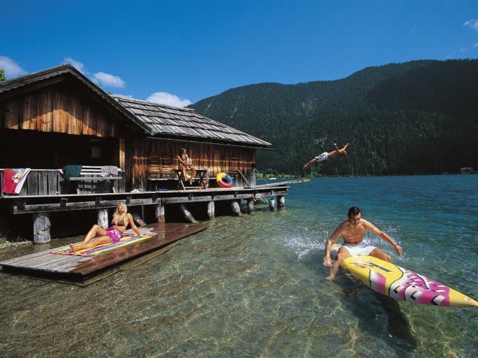 Familie vergnügt sich am Weissensee in Kärnten mit Surfbrett im Sommer. JUFA Hotels bietet Ihnen den Ort für erlebnisreichen Natururlaub für die ganze Familie.