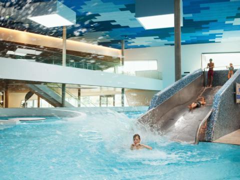 Kinder rutschen von der Wasserrutsche in der Therme Wien. JUFA Hotels bietet erlebnisreichen Städtetrip für die ganze Familie und den idealen Platz für Ihr Seminar.