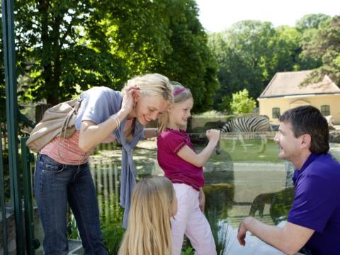 Familie beim Zoobesuch im Tiergarten Schönbrunn in Wien. JUFA Hotels bietet kinderfreundlichen und erlebnisreichen Urlaub für die ganze Familie.