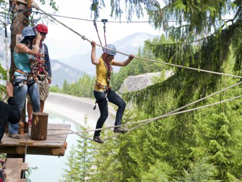 Erwachsene klettern im Waldseilpark-Golm im Montafon in der Nähe vom JUFA Hotel Montafon. Der Ort für kinderfreundlichen und erlebnisreichen Urlaub für die ganze Familie.