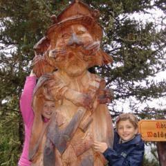 Zwei Kinder vor König Waldgeist Holzstatue im Wandergebiet Hochrindl in der Nähe vom JUFA Hotel Nockberge - Almerlebnis. Der Ort für erholsamen Familienurlaub und einen unvergesslichen Winter- und Wanderurlaub.