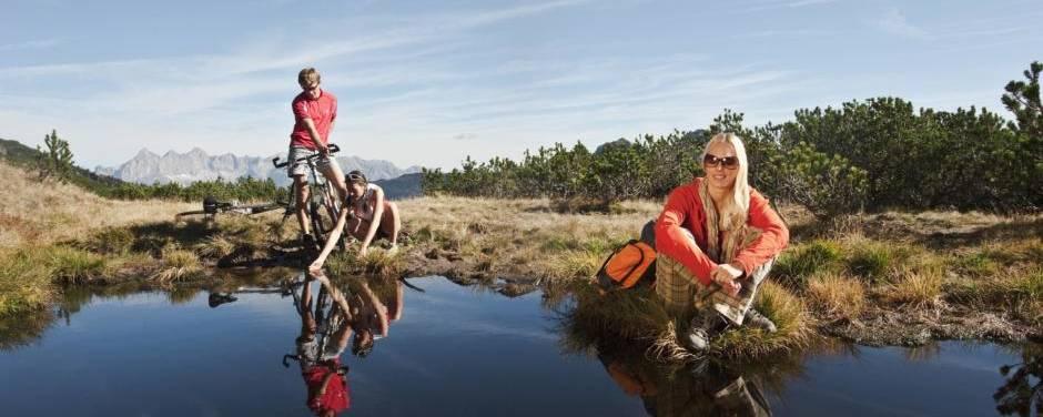 Sportler machen Pause beim Wandern und Mountainbiken an einem Bergsee in Altenmarkt-Zauchensee in der Nähe von JUFA Hotels. Der Ort für erholsamen Familienurlaub und einen unvergesslichen Winter- und Wanderurlaub.