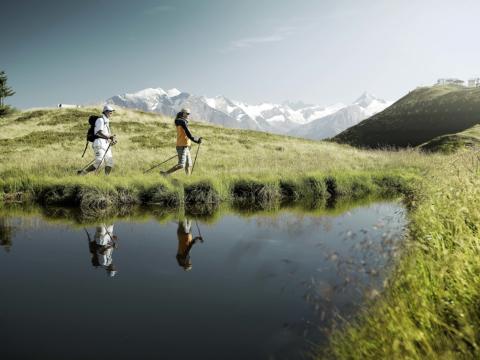Paar wandert bei herrlichem Sommerwetter auf der Schmittenhöhe. JUFA Hotels bieten erholsamen Familienurlaub und einen unvergesslichen Winter- und Wanderurlaub.