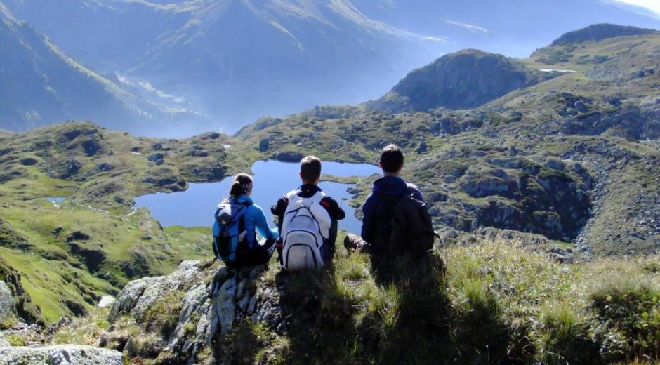 Wanderer machen Pause auf einem Felsen mit Blick auf einen Bergsee im Wandergebiet Oberwölz in der Nähe von JUFA Hotels. Der Ort für erholsamen Familienurlaub und einen unvergesslichen Winter- und Wanderurlaub.