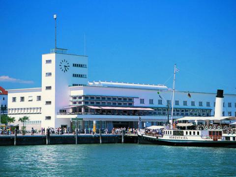 Sie sehe das Zeppelin Museum in Friedrichshafen am Bodensee mit einem Ausflugsboot. JUFA Hotels bietet kinderfreundlichen und erlebnisreichen Urlaub für die ganze Familie.