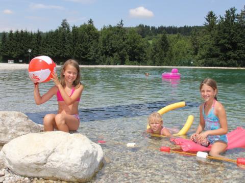 Kinder planschen am Ufer des Badesees St. Konrad im Salzkammergut an einem heißen Sommertag. JUFA Hotels bietet kinderfreundlichen und erlebnisreichen Urlaub für die ganze Familie.