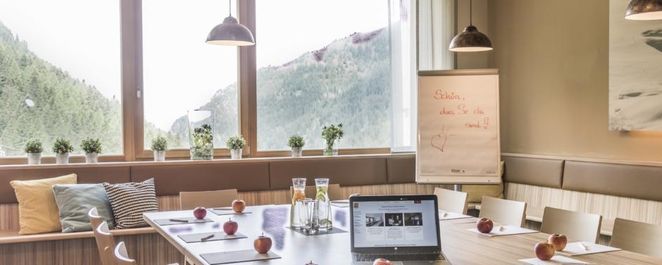 Besprechungstischmit Laptop und Äpfeln im Restaurantbereicht im JUFA Hotel Malbun Alpin-Resort. Der Ort für erholsamen Familienurlaub und einen unvergesslichen Winter- und Wanderurlaub.