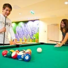 Sie sehen zwei Personen beim Billardspielen im JUFA Hotel Waldviertel- Der Ort für erholsamen Familienurlaub und einen unvergesslichen Winter- und Wanderurlaub.