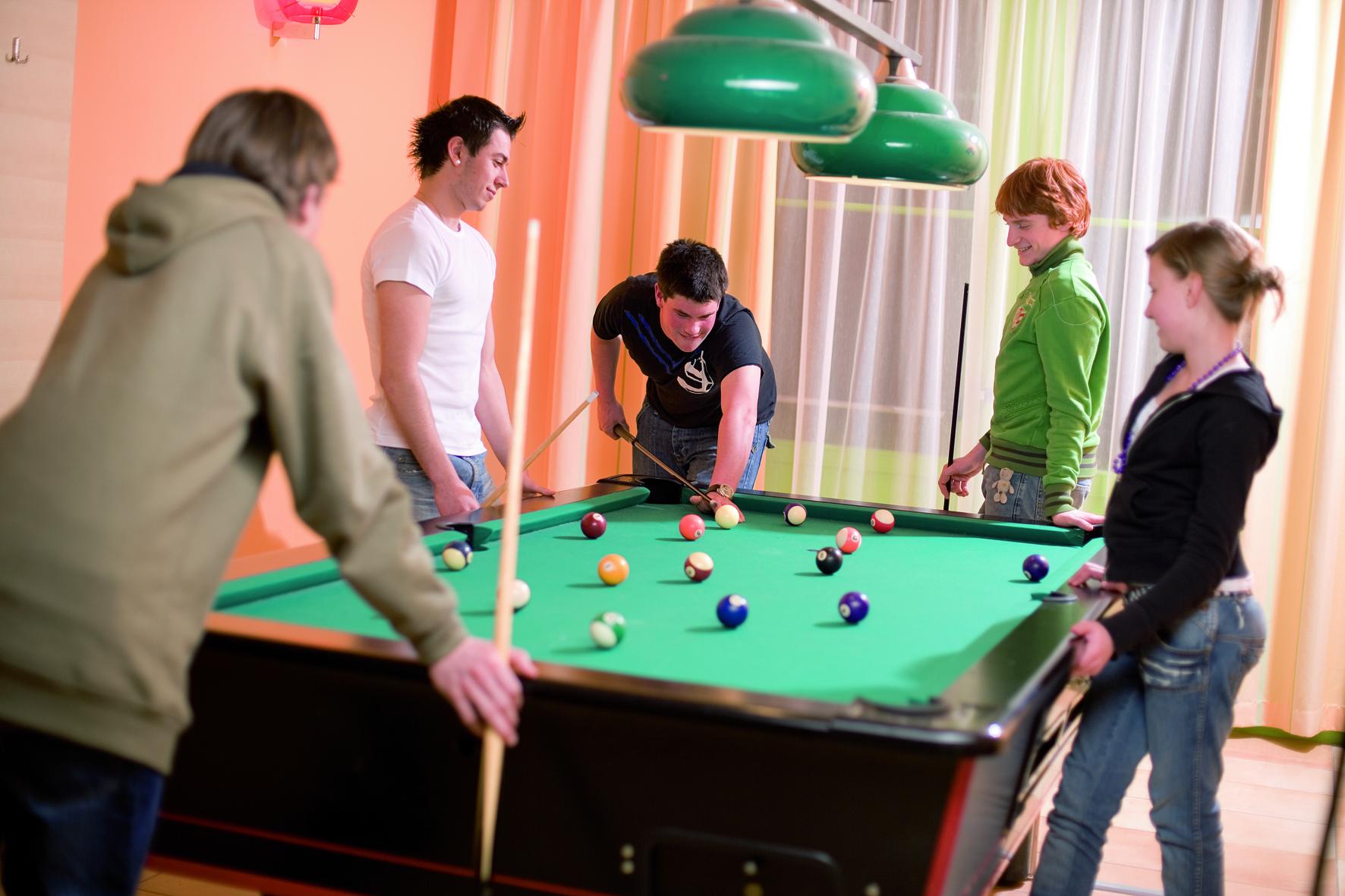 Sie sehen einen Billardtisch mit Teenagern die Billard spielen.Die Zeit spielend und abwechslungsreich verbringen im JUFA Hotel Wipptal. Der Ort für erholsamen Familienurlaub und einen unvergesslichen Winter- und Wanderurlaub.