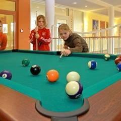Kinder spielen Billard auf der Galerie im JUFA Kempten Familien-Resort. Der Ort für kinderfreundlichen und erlebnisreichen Urlaub für die ganze Familie.