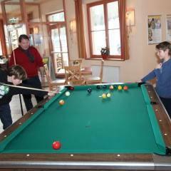 Familie beim Billardspielen in der Lobby im JUFA Hotel Nockberge - Almerlebnis. Der Ort für erholsamen Familienurlaub und einen unvergesslichen Winter- und Wanderurlaub.