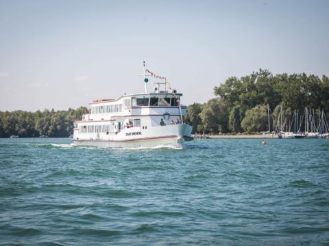 Ein Schiff der Bodenseeschiffahrt fährt im Sommer über den wunderschönen Bodensee. JUFA Hotels bietet tollen Sommerurlaub an schönen Seen für die ganze Familie.