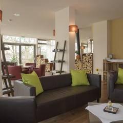 Sie sehen ein Sofa und einen Sessel im Cafebereich mit Wandstrahlern. JUFA Hotel Wangen Sport-Resort. Der Ort für erfolgreiches Training in ungezwungener Atmosphäre für Vereine und Teams.