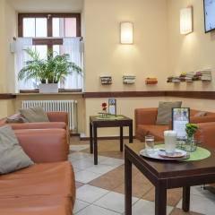 Sie sehen einen Teil des Cafés im JUFA Hotel Meersburg mit Sofas, Couchtisch, Grünpflanze und Büchern an der Wand. Der Ort für tollen Sommerurlaub an schönen Seen für die ganze Familie
