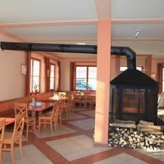Sie sehen einen Kamin im Café mit Holz im JUFA Hotel Nockberge - Almerlebnis.Der Ort für erholsamen Familienurlaub und einen unvergesslichen Winter- und Wanderurlaub.