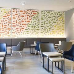Café und Lobby mit Wandspruch im JUFA Hotel Graz City. Der Ort für erlebnisreichen Städtetrip für die ganze Familie und der ideale Platz für Ihr Seminar.