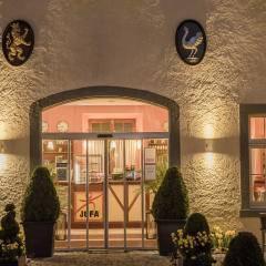 Sie sehen den beleuchteten Eingangsbereich mit Grünpflanzen und Gartentischen im JUFA Hotel Meersburg. Der Ort für tollen Sommerurlaub an schönen Seen für die ganze Familie.