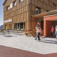 Eingangsbereich und Sonnenterrasse im Sommer mit Sonnenschein vom JUFA Hotel Malbun-Alpin-Resort. Der Ort für erholsamen Familienurlaub und einen unvergesslichen Winter- und Wanderurlaub.
