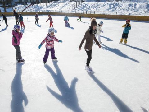 Kinder beim Eislaufen auf dem Eislaufplatz in Altenmarkt-Zauchensee. JUFA Hotels bietet erholsamen Familienurlaub und einen unvergesslichen Winterurlaub.