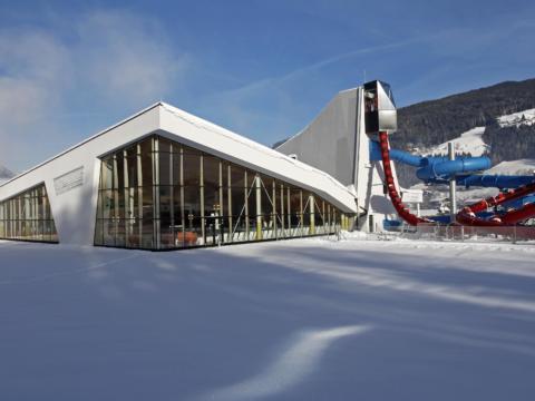 Schneebedeckte Aussenansicht der Erlebnis-Therme Amadé im Winter in der Nähe vom JUFA Hotel Altenmarkt. Der Ort für erholsamen Familienurlaub und einen unvergesslichen Winter- und Wanderurlaub.