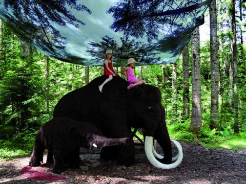 Zwei Mädchen sitzen auf einem Mammut im Familien Erlebnispark Gosau am Dachstein. JUFA Hotels bietet kinderfreundlichen und erlebnisreichen Urlaub für die ganze Familie.