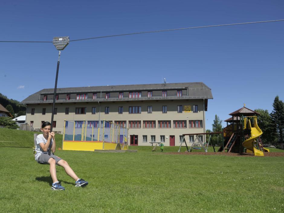 Sie sehen ein Kind spielend mit einem Flying Fox beim JUFA Hotel Lungau im Sommer. Der Ort für erholsamen Familienurlaub und einen unvergesslichen Winter- und Wanderurlaub.