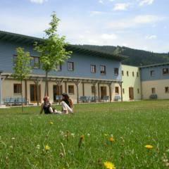 Zwei Frauen sitzen in der Blumenwiese vor dem JUFA Mariazell - Erlaufsee Sport-Resort. Der Ort für erfolgreiches Training in ungezwungener Atmosphäre für Vereine und Teams.
