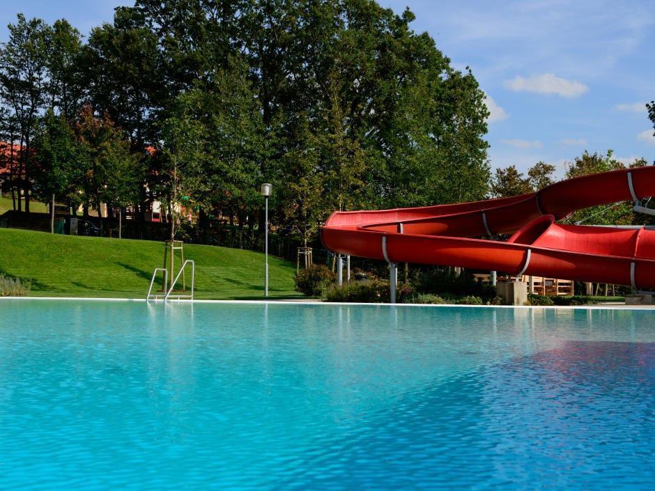 Freibad mit roter Rutsche in Neutal. JUFA Hotels bietet Ihnen den Ort für erlebnisreichen Natururlaub für die ganze Familie.