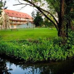 Aussenansicht mit Bach und Wiese im Sommer vom JUFA Hotel Nördlingen. Der Ort für kinderfreundlichen und erlebnisreichen Urlaub für die ganze Familie.