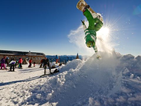 Snowboarder bei gewagtem Stunt auf der Gemeindealpe Mitterbach am Erlaufsee mit Skifahrern im Hintergrund. JUFA Hotels bietet erholsamen Familienurlaub und einen unvergesslichen Winterurlaub.