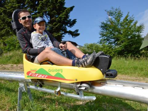 Vater und Sohn sausen mit einer Sommerrodel des Grünberg Flitzers im Salzkammergut ins Tal. JUFA Hotels bietet kinderfreundlichen und erlebnisreichen Urlaub für die ganze Familie.