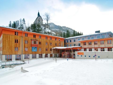 Hotelansicht mit Eingang im Winter vom JUFA Hotel Mariazell Sigmundsberg. Der Ort für erholsamen Familienurlaub und einen unvergesslichen Winter- und Wanderurlaub.
