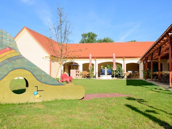 Sie sehen den Innenhof mit Arkaden, Sonnenschirmen, einem Teil der Terrasse und einer Kinderrutsche auf einer grünen Wiese im JUFA Hotel Neutal Landerlebnis. Der Ort für erlebnisreichen Natururlaub für die ganze Familie.