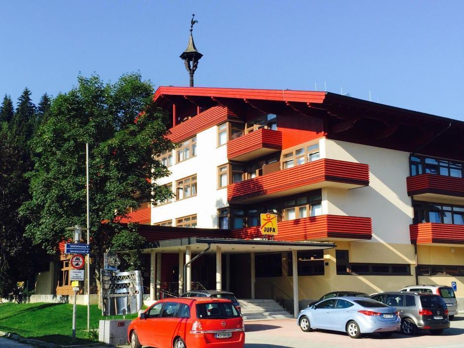 Aussenansicht mit Parkplatz im Sommer vom JUFA Hotel Altenmarkt. Der Ort für erholsamen Familienurlaub und einen unvergesslichen Winterurlaub.
