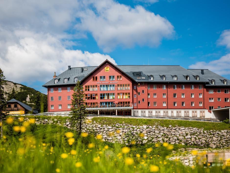 Frontale Hotelansicht mit blühender Wiese im Sommer vom JUFA Hotel Hochkar Sport-Resort. Der Ort für erfolgreiches Training in ungezwungener Atmosphäre für Vereine und Teams.