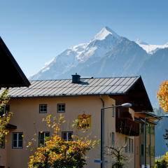 Aussenansicht mit Bergblick im Sommer vom JUFA Hotel Kaprun. Der Ort für erholsamen Familienurlaub und einen unvergesslichen Winter- und Wanderurlaub.