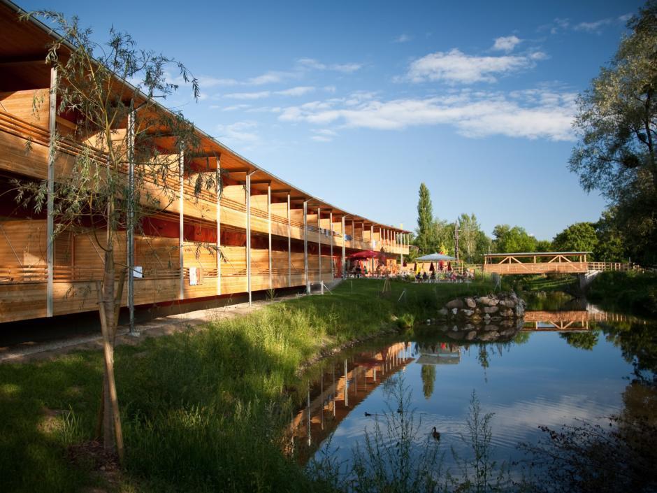 Sie sehen die Hotelansicht mit den Balkonen der Zimmer, blauem Himmel und ein Bachbeet vam JUFA Hotel Leibnitz-Sport-Resort. Der Ort für erfolgreiches Training in ungezwungener Atmosphäre für Vereine und Teams.