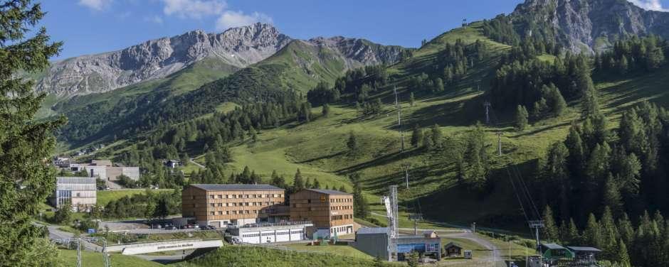 Hotelansicht mit Bergen direkt beim JUFA Hotel Malbun Alpin-Resort im Sommer. Der Ort für erholsamen Familienurlaub und einen unvergesslichen Winter- und Wanderurlaub.