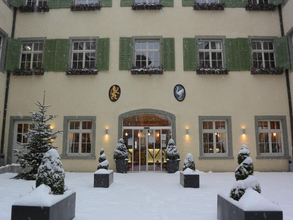 Sie sehen den Innenhof mit dem Eingangsbereich im Winter mit Schnee vom JUFA Hotel Meersburg. Der Ort für entspannte Urlaube für die ganze Familie.