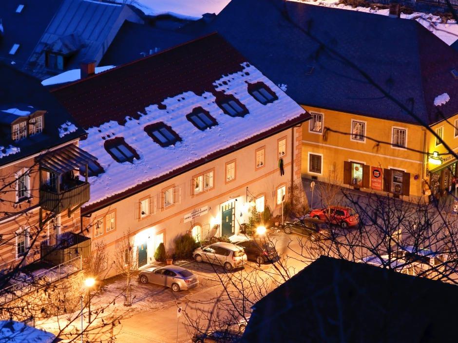 Sie sehen die Aussenansicht aus der Vogelperspektive mit dem Eingang des JUFA Hotels Murau bei Abenddämmerung im Winter. Ort für erholsamen Familienurlaub und einen unvergesslichen Winter- und Wanderurlaub.