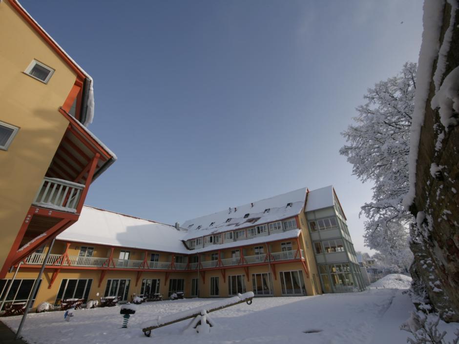 Aussenansicht mit verschneitem Spielplatz vom JUFA Hotel Nördlingen. Der Ort für kinderfreundlichen und erlebnisreichen Urlaub für die ganze Familie.