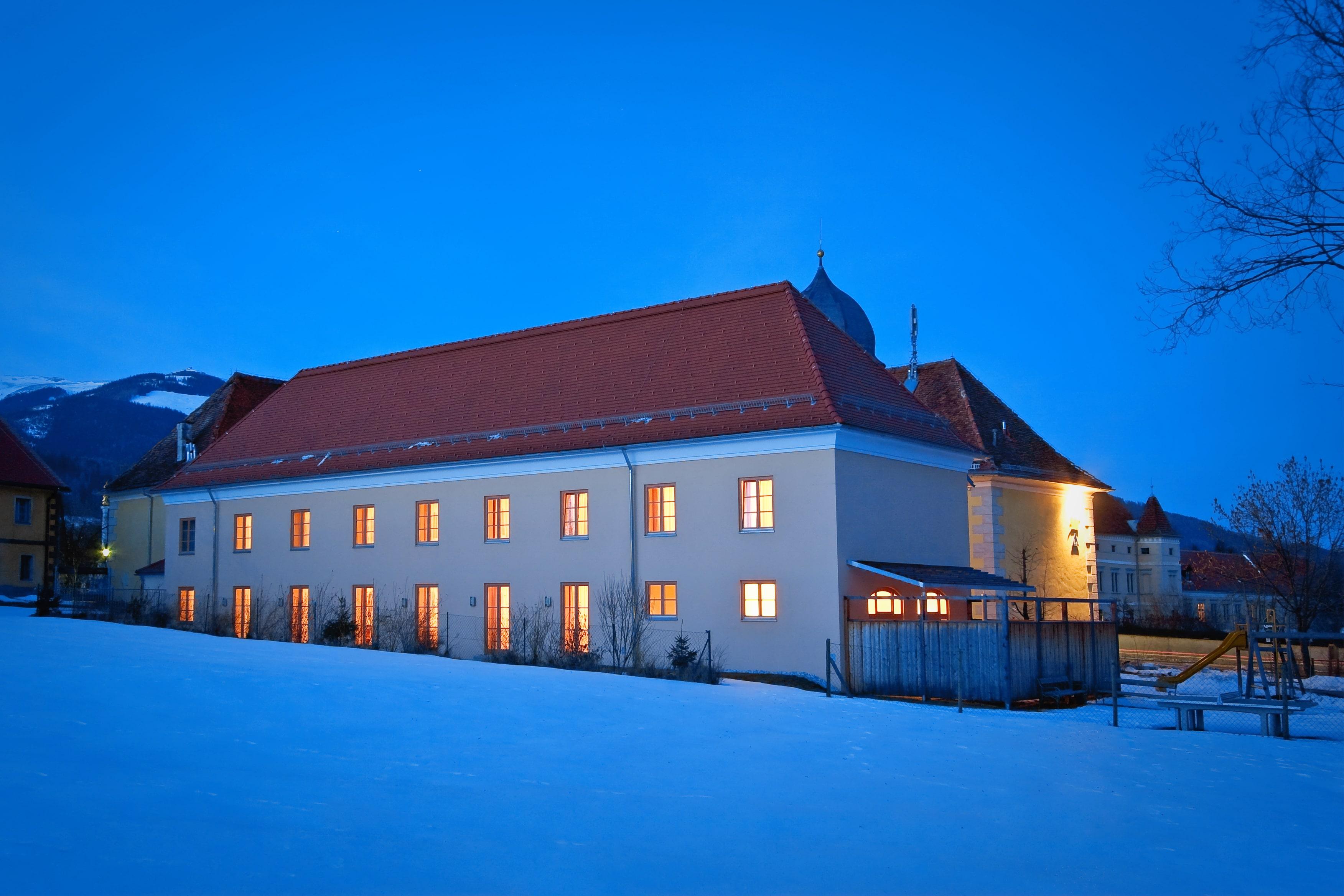 Sie sehen die Aussenansicht im Winter des Hotels mit beleuchteten Fenstern bei Abendstimmung beim JUFA Hotel Seckau. Der Ort für erholsamen Familienurlaub und einen unvergesslichen Winter- und Wanderurlaub.