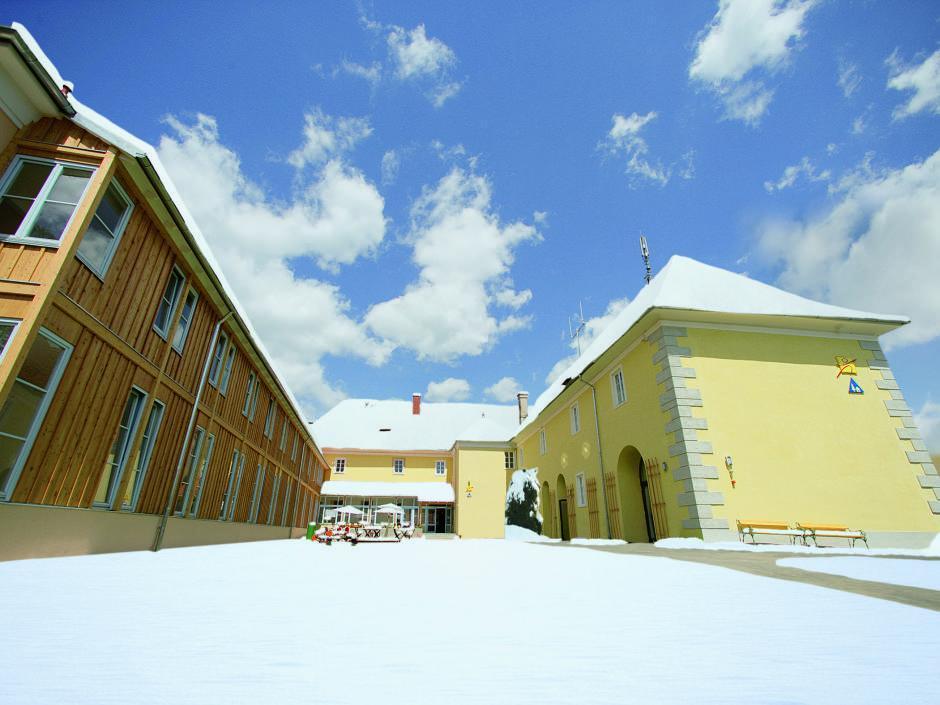 Sie sehen die Aussenansicht mit einem Weg zum JUFA Hotel Seckau im Winter. Der Ort für erholsamen Familienurlaub und einen unvergesslichen Winter- und Wanderurlaub.