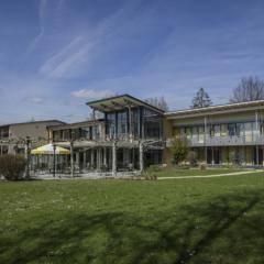 Aussenansicht mit grüner Wiese im Sommer vom JUFA Hotel Wangen Sport-Resort. Der Ort für erfolgreiches Training in ungezwungener Atmosphäre für Vereine und Teams.