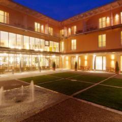 Innenhof vom JUFA Kempten Familien-Resort  mit Brunnen bei Abendstimmung. JUFA Hotels bietet kinderfreundlichen und erlebnisreichen Urlaub für die ganze Familie.