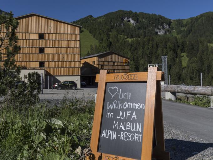 Hotelansicht vom JUFA Hotel Malbun Alpin-Resort mit einer Tafel mit Willkommensgruß im Vordergrund. Der Ort für erholsamen Familienurlaub und einen unvergesslichen Winter- und Wanderurlaub.