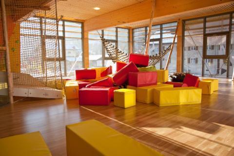 Sie sehen die Indoor-Kindererlebniswelt mit roten und gelben Würfel vor einer Fensterfront im JUFA Hotel Montafon. Der Ort für erholsamen Familienurlaub und einen unvergesslichen Winter- und Wanderurlaub.