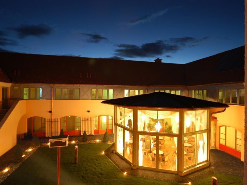 Sie sehen die Aussenansicht des Innenhofs mit beleuchteten Pavillion in der Abenddämmerung im JUFA Hotel Pöllau-Bio-Landerlebnis. Der Ort für erlebnisreichen Natururlaub für die ganze Familie.
