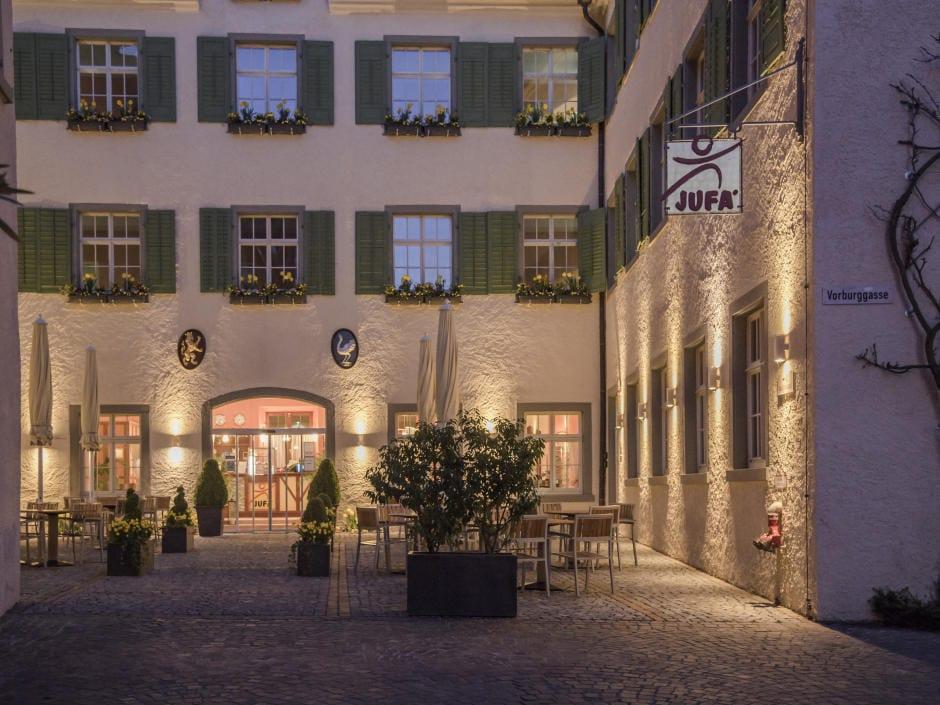 Sie sehen die beleuchtete Terrasse im Eingangsbereiches des JUFA Hotels Meersburg. Der Ort für tollen Sommerurlaub an schönen Seen für die ganze Familie.