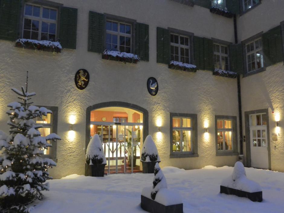 Sie sehen den Innenhof des JUFA Hotels in Meersburg bei Winter und mit Schnee. Die Fenster und die Eingangstür sind beleuchtet. JUFA Hotel Meersburg ein Ort für einen entspannten Urlaub für die ganze Familie.